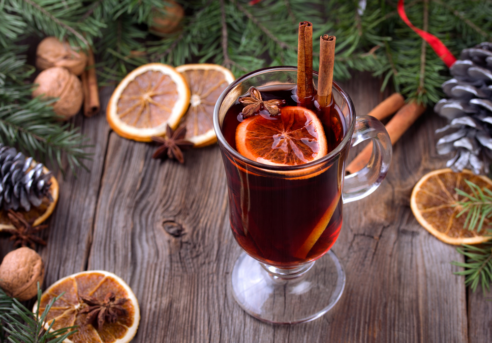 Mulled wine and spices. Sliced dried orange, cinnamon sticks and anise stars with pine brunch and candle. Christmas decoration over wooden background. .